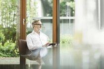 Uomo seduto con tablet sulla sedia nel suo soggiorno guardando attraverso la finestra — Foto stock