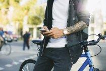 Adolescente con una bici fixie, utilizzando smartphone — Foto stock