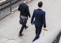 Empresarios caminando con maletas con ruedas - foto de stock