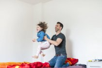 Father playing with daughter on bed — Stock Photo