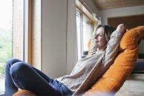 Femme souriante relaxante en fauteuil — Photo de stock
