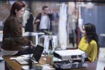 Две женщины разговаривают в салоне моды — стоковое фото
