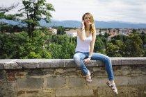 Giovane donna seduta su un muro telefonare con smartphone — Foto stock