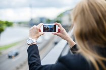 Back view of woman with smartphone — Stock Photo