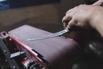 Fälscher schleift Messer in Werkstatt — Stockfoto