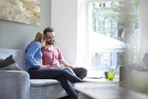 Heureux jeune couple assis sur le canapé — Photo de stock