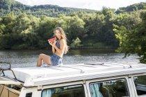 Женщина, сидящая на крыше фургона у озера — стоковое фото