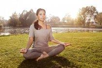Женщина расслабляется в позе йоги Лотоса — стоковое фото