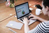 Mujer en el escritorio usando el ordenador portátil trabajando en el cálculo - foto de stock