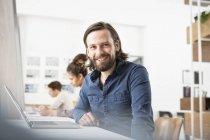 Улыбающийся человек в офисе с ноутбуком смотрит в камеру — стоковое фото