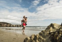 Happy young man carrying girlfriend piggyback on the beach — Stock Photo