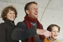 Гордий батько посміхаючись, весело з синами — стокове фото