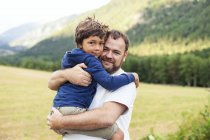 Portrait of father and little son hugging in nature — Stock Photo