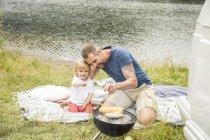 Vater und Sohn beim Grillen am See — Stockfoto
