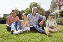 Портрет счастливых родителей с внуками в саду — стоковое фото