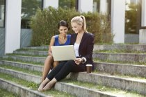 Two businesswomen sitting on stairs outside using a laptop — Stock Photo