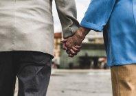 Пожилая пара держится за руки — стоковое фото