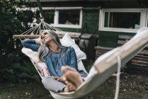 Nachdenkliche Frau liegt in Hängematte — Stockfoto