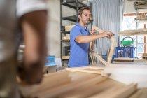 Чоловік дивиться на дерев'яному каркасі, на полотні підготовки в майстерні — стокове фото