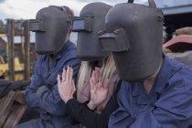 Три человека в сварочных шлемах сидят на улице — стоковое фото