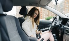 Woman in car fastening her seat belt — Stock Photo