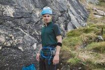 Ritratto di arrampicatore sicuro in piedi sulla parete rocciosa — Foto stock