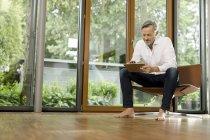 Hombre descalzo sentado en silla en su sala de estar usando la tableta - foto de stock