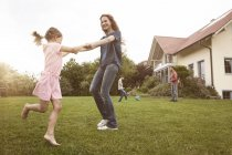 Mother and daughter dancing in garden with family in background — Stock Photo