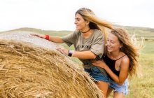 Two best friends climbing on straw bale — Stock Photo