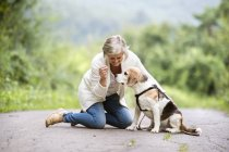 Senior woman playing with dog on the ground in nature — Stock Photo