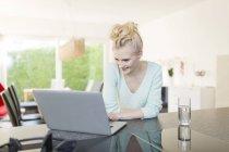 Woman using laptop on kitchen counter — Stock Photo