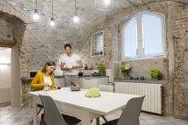 Couple dans la cuisine, femme, préparation de salade de fruits, l'homme se tenant près de la table — Photo de stock