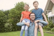 Портрет счастливого отца с двумя детьми в саду — стоковое фото