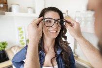 Man putting woman on oversized glasses — Stock Photo