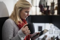 Young woman reading on digital tablet, holding cup of coffee — Stock Photo