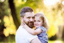 Retrato de pai feliz segurando a filhinha sorridente em seus braços — Fotografia de Stock