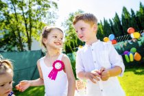Happy little children having birthday party in the garden — Stock Photo