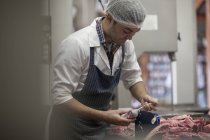 Butcher packing raw meat in butchery — Stock Photo