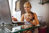 Donna incinta con figlio che utilizza il computer portatile — Foto stock