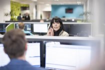Woman on the phone in office looking at colleague — Stock Photo