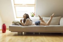 Розслабленої жінка, лежачи на дивані — стокове фото
