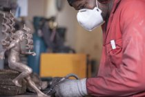 Man working on bronze figurine, side view — Stock Photo