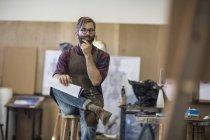 Artiste en studio avec la pensée de carnet de croquis — Photo de stock