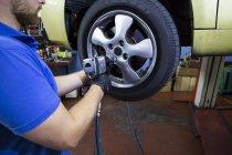Механік кріплення колеса автомобіля у семінарі — стокове фото