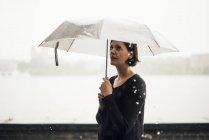 Mulher com um guarda-chuva num dia de chuva — Fotografia de Stock