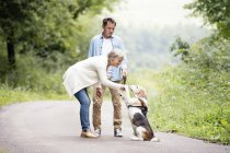 Senior couple playing with dog in nature — Stock Photo