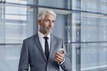Homme d'affaires confiant maintenant téléphone cellulaire au bureau moderne — Photo de stock