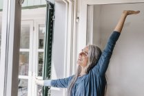 Woman standing next to window — Stock Photo