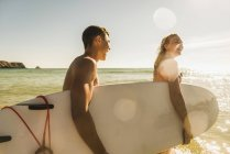 Teenage couple carrying surfboard at the sea — Stock Photo
