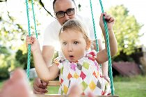 Father pushing daughter on swing in park — Stock Photo